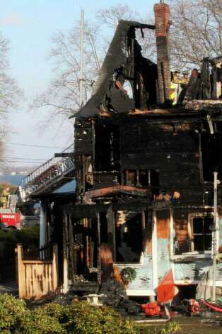 A section of a house where an early morning fire left five people dead is seen Sunday, Dec. 25, 2011 in Stamford, Conn. Officials said the fire, which was reported shortly before 5 a.m., killed two adults and three children. Two others escaped. Their names have not been released. (AP Photo/Tina Fineberg) Photo: Tina Fineberg, Associated Press / AP2011