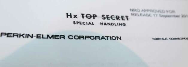 "This Thursday, Dec. 1, 2011 photo shows the crossed-out ""top secret"" designation from recently declassified documents about the Hexagon spy satellite program in Danbury, Conn. At one point in the 1970s there were more than 1,000 people in the Danbury area working on The Secret. And though they worked long hours under intense deadlines, sometimes missing family holidays and anniversaries, they could tell no one - not even their wives and children - what they did. Photo: Kathy Willens"