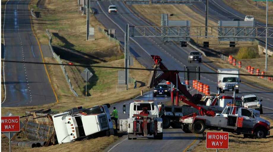 Wrecker crews work to unload and move a tractor-trailer that was carrying a load of large pipes and crashed Monday where eastbound U.S. 90 meets Loop 410 West. Police said the truck was reported stolen out of Bexar  County and that the driver fled. The ramp connecting the two highways was closed for hours. Photo: SAN ANTONIO EXPRESS-NEWS