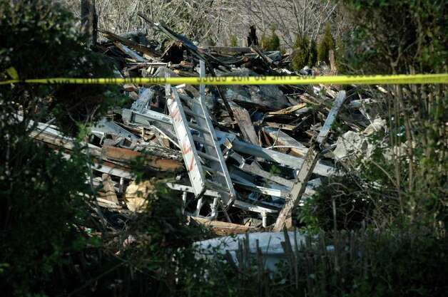 On Monday, Dec. 26, 2011, an excavator took down the house at 2267 Shippan Ave. in Stamford, Conn., the scene of a massive, three-alarm fire on Christmas morning that killed three young girls and their grandparents. Photo: Cathy Zuraw / Stamford Advocate