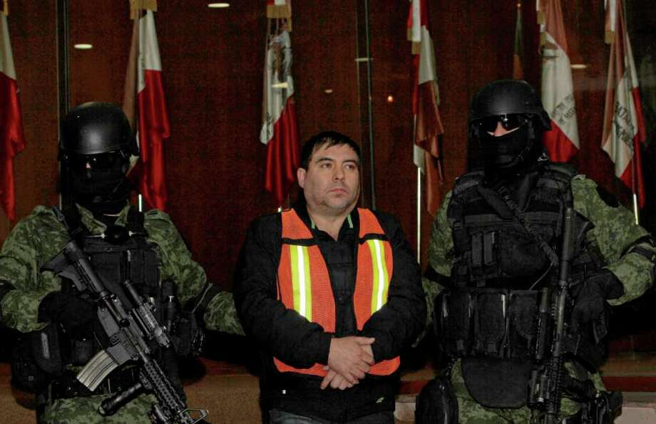 """Felipe Cabrera Sarabia, alias """"El Inge,"""" is shown to the press under the custody of army soldiers at the federal organized crime investigations headquarters (SIEDO) in Mexico City, Monday Dec. 26, 2011. According to federal authorities, Sarabia is a close associate and head of security for Mexico's most wanted criminal, Joaquin Guzman Loera, alias """"El Chapo,"""" leader of the Sinaloa cartel in the Durango mountains region.   Authorities say Sarabia was captured on Friday in the capital of Sinaloa state. Photo: AP"""