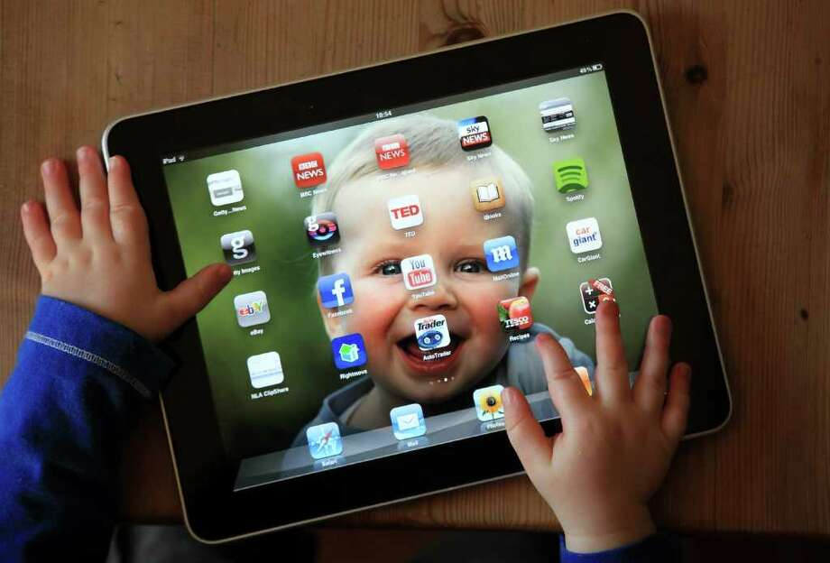 MATT CARDY : GETTY IMAGES SAFEGUARDING A VALUABLE: In this photo illustration, a 13-month-old uses an iPad. There are steps you can take to protect your tablet. Photo: Matt Cardy / 2011 Getty Images