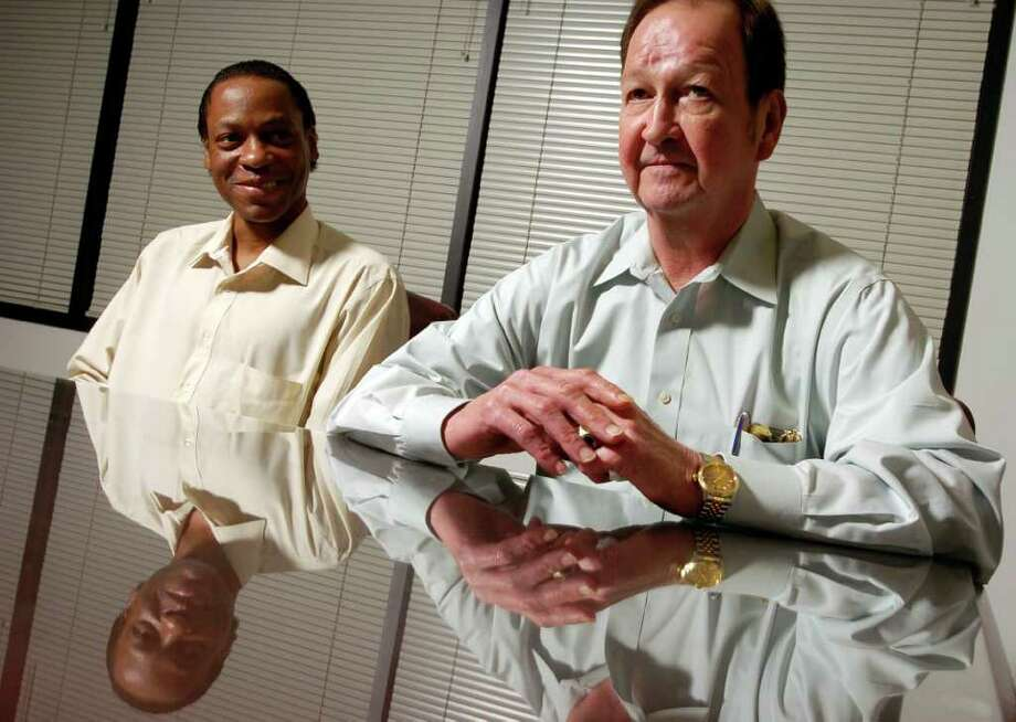 CHRISTOBAL PEREZ : CHRONICLE FILE REFLECTING: John Lawrence, right, and Tyron Garner discuss their experience in an interview in Houston lawyer Mitchell Katine's office in April 2004, almost a year after the Supreme Court ruled that states may not criminalize private homosexual conduct. Photo: Christobal Perez / Houston Chronicle