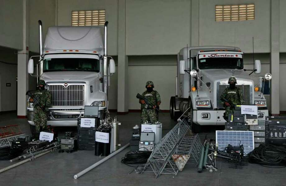FILE - In this Sept. 8, 2011 file photo, members of the Navy stand guard over seized telecommunications equipment, allegedly built by the Zetas drug cartel, during a media presentation in Veracruz, Mexico. The Mexican army and marines have seized hundreds of pieces of communications equipment in at least three operations since September that offer a firsthand look at a surprisingly far-ranging and sophisticated infrastructure. According to authorities, the network was built around 2006 by the Gulf cartel, a narcotics-trafficking gang that employed a group of enforcers known as the Zetas who had defected from Mexican army special forces. Photo: AP