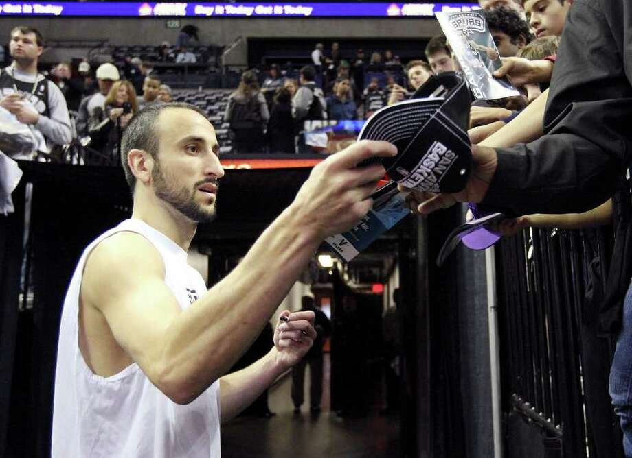 San Antonio Spurs' Manu Ginobili signs autographs for fans before the game with the Memphis Grizzlies Monday Dec. 26, 2011 at the AT&T Center. Photo: EDWARD A. ORNELAS, Express-News / SAN ANTONIO EXPRESS-NEWS (NFS)