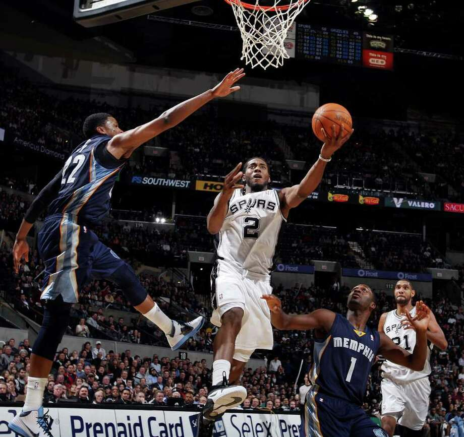 San Antonio Spurs' Kawhi Leonard shoots between Memphis Grizzlies' Rudy Gay (left) and Memphis Grizzles' Jeremy Pargo as San Antonio Spurs'  Tim Duncan looks on during second half action Monday Dec. 26, 2011 at the AT&T Center. The Spurs won 95-82. Photo: EDWARD A. ORNELAS, Express-News / SAN ANTONIO EXPRESS-NEWS (NFS)