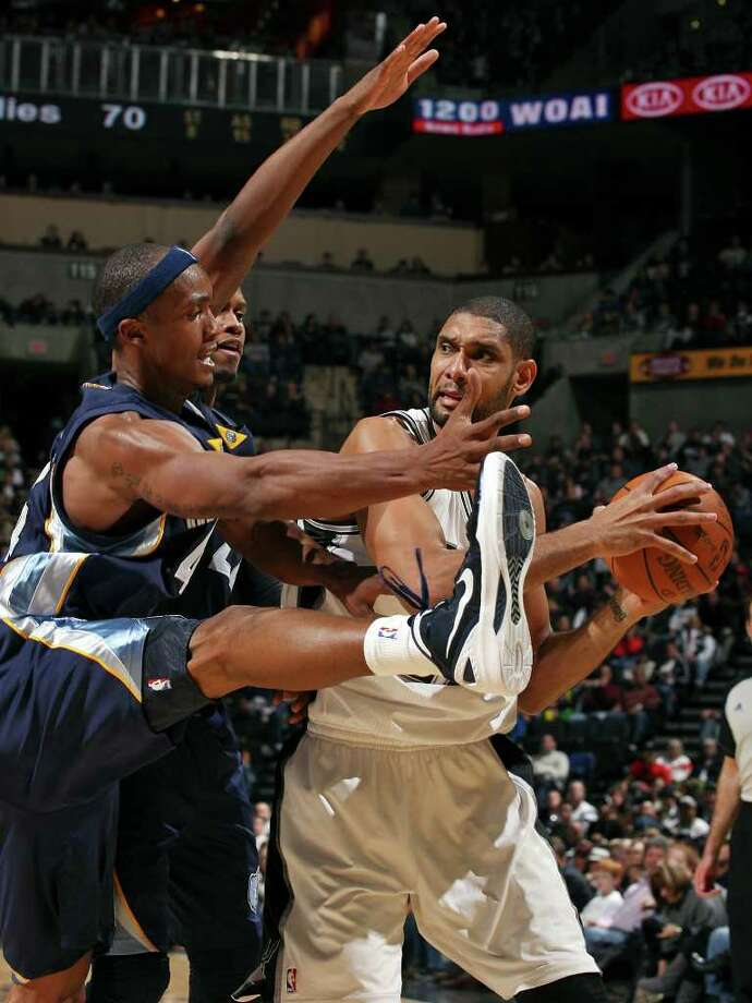 San Antonio Spurs' Tim Duncan looks for room around Memphis Grizzlies' Dante Cunningham and Memphis Grizzles' Rudy Gay (rear) during second half action Monday Dec. 26, 2011 at the AT&T Center. The Spurs won 95-82. Photo: EDWARD A. ORNELAS, Express-News / SAN ANTONIO EXPRESS-NEWS (NFS)