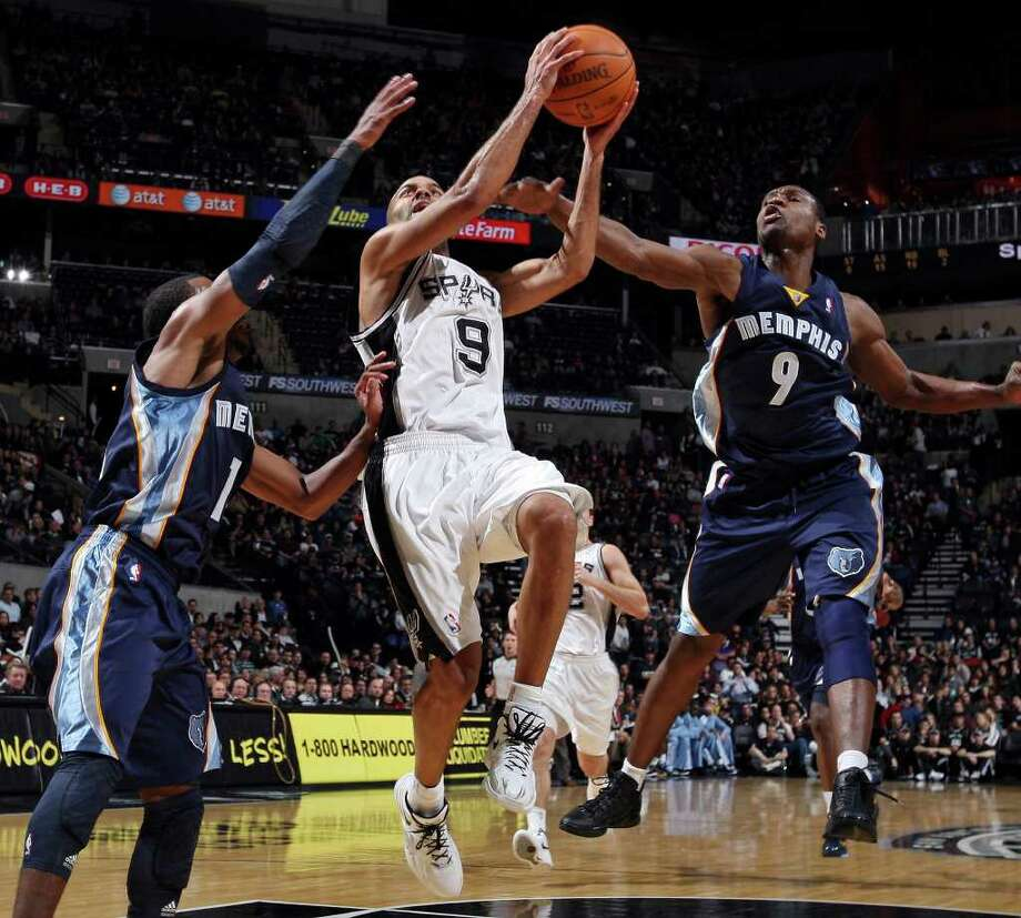 San Antonio Spurs' Tony Parker drives to the basket between Memphis Grizzlies' Mike Conley (left) and Memphis Grizzles' Tony Allen during second half action Monday Dec. 26, 2011 at the AT&T Center. Parker was fouled on the play by Allen. The Spurs won 95-82. Photo: EDWARD A. ORNELAS, Express-News / SAN ANTONIO EXPRESS-NEWS (NFS)