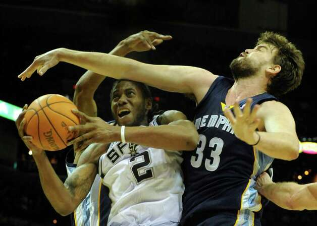 Kawhi Leonard (2) of the San Antonio Spurs is fouled by Marc Gasol (33) of the Memphis Grizzlies during NBA action at the AT&T Center on Monday, Dec. 26, 2011. BILLY CALZADA / gcalzada@express-news.net