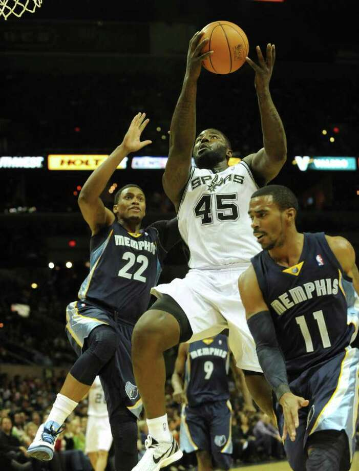 DeJuan Blair of the San Antonio Spurs (45) drives to the basket between Rudy Gay (22) and Mike Conley (11) of the Memphis Grizzlies during NBA action at the AT&T Center on Monday, Dec. 26, 2011. BILLY CALZADA / gcalzada@express-news.net
