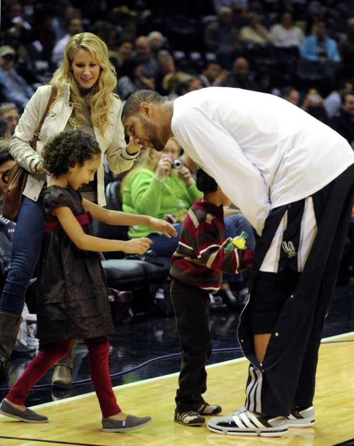 San Antonio Spurs forward Tim Duncan greets his wife, Amy, and children prior to the team's season-opening game against the Memphis Grizzlies at the AT&T Center on Monday, Dec. 26, 2011. BILLY CALZADA / gcalzada@express-news.net