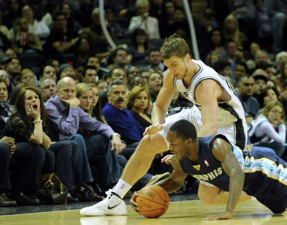 Jeremy Pargo of the Memphis Grizzlies dives for the ball as Tiago Splitter of the San Antonio Spurs chases during second-half NBA action at the AT&T Center on Monday, Dec. 26, 2011. BILLY CALZADA / gcalzada@express-news.net