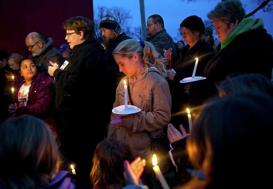 Megan Lehman (center) stands among a crowd of people gathered for a candlelight vigil for 9-year-old Aliahna Lemmon, who was later found dead. Photo: SWIKAR PATEL, JOURNAL-GAZETTE
