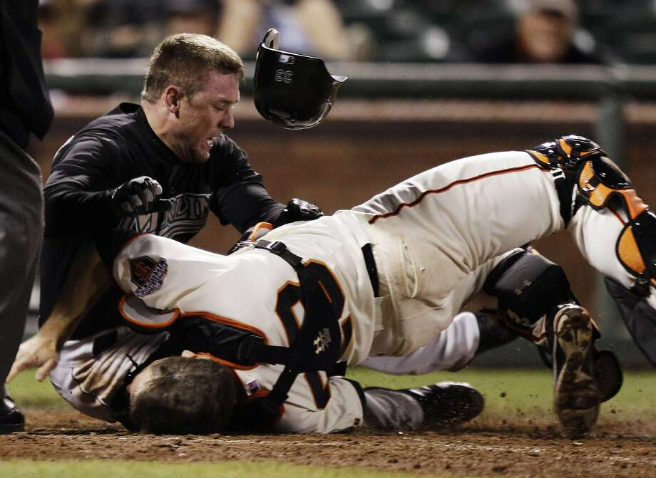 Florida Marlins' Scott Cousins collides with San Francisco Giants catcher Buster Posey in the 12th inning on Wednesday. Photo: Marcio Jose Sanchez, AP