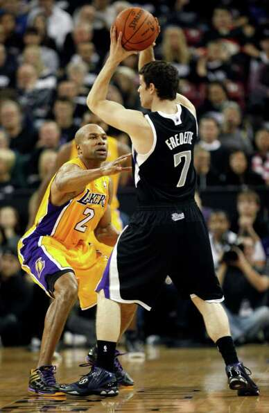 Los Angeles Lakers guard Derek Fisher, left, defends against Sacramento Kings guard Jimmer Fredette