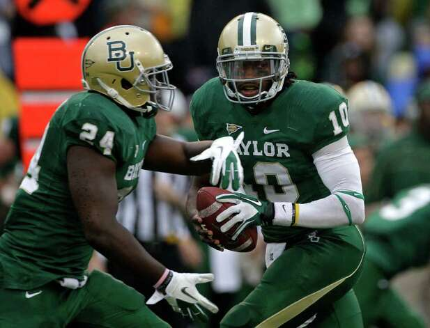 Baylor quarterback Robert Griffin III fakes the hand off to Terrance Ganaway (24) in the first half of an NCAA college football game against Texas Saturday, Dec. 3, 2011, in Waco, Texas. Griffin III ran for two touchdowns and passed for two more to lead No. 19 Baylor to a 48-24 win over Texas. Photo: AP