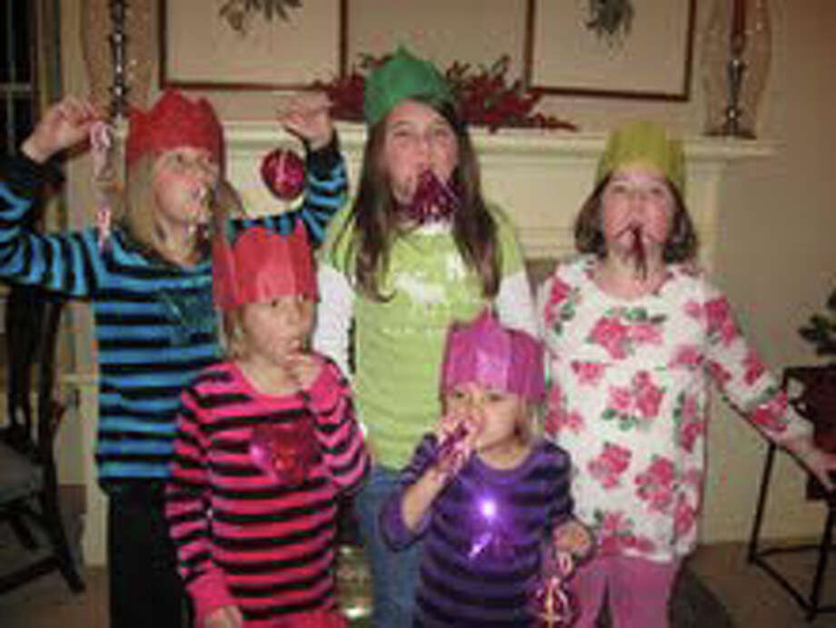 Celebrating with the spoils from their Christmas Crackers, including noisemakers, paper hats, treats and a motto from George Washington are, front row, Hadley and Delaney Bennhoff; back row, Mallory Bennhoff, Gwenan Walker and Anna Reed. Photo: Contributed Photo