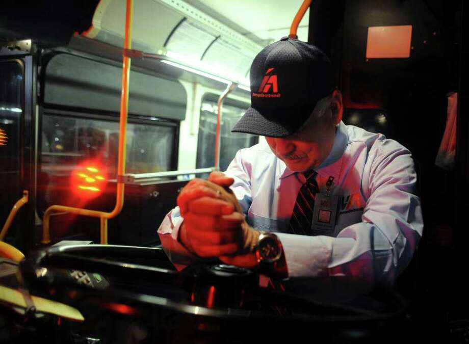 Gilbert M. Perez prays before pulling out of VIA headquarters for his day as the driver of the Route 609 bus. Photo: BILLY CALZADA, Billy Calzada / gcalzada@express-news.net