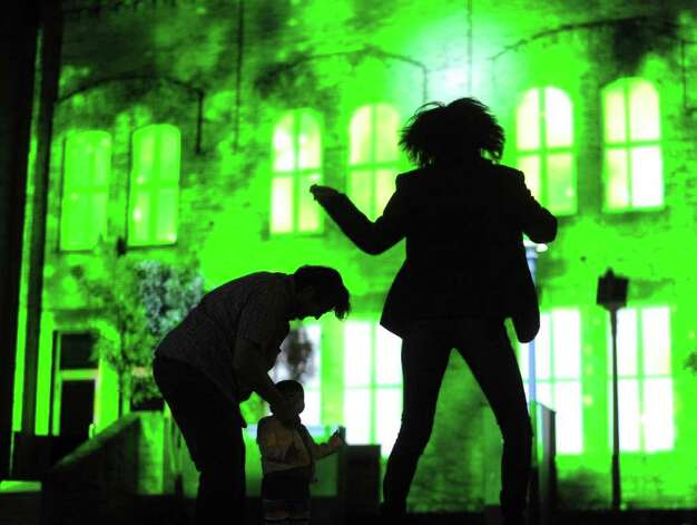 Aura Moreno dances on the lawn by the Magik Theatre as a 3D projection mapping display by Scott Justis of LD Systems is projected during a dress rehearsal in preparation for Luminaria on Friday night, March 11, 2011. Photo: BILLY CALZADA, Billy Calzada / gcalzada@express-news.net