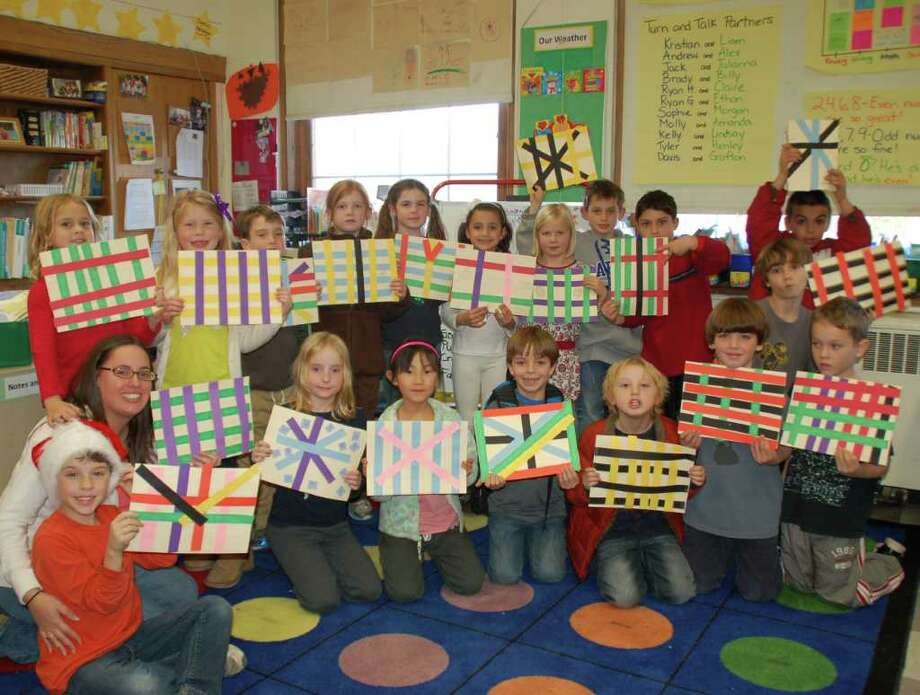 Pictured is Sarah Obuchowski and her class displaying their handmade mkekas which serves as a mat for the Kwanzaa feast. Photo: Contributed Photo