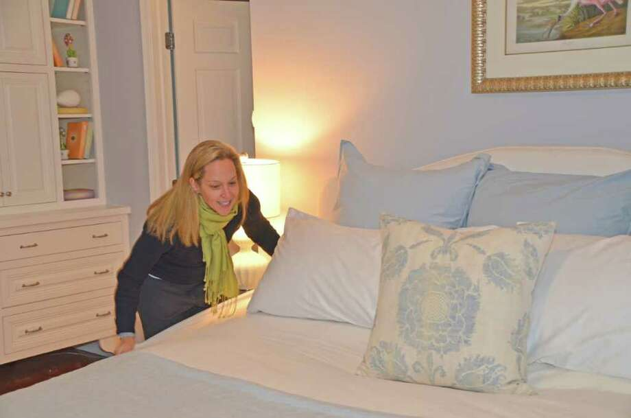 Liza Brasini, designer for Stage to Show, straightens up the bed in the master bedroom in one of the homes recently finished in Darien.  She and Stage to Show owner Lisa Hynes staged this particular house, after it had been on the market for a year, and it sold within 10 days.  Continue viewing the following photographs to see several before and after shots of this home. Photo: Jeanna Petersen Shepard