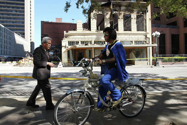 An Elvis impersonator rides by as pedestrians, bikers and others hang out at Main Plaza to watch the remains of the Wolfson Building across the street on East Commerce, Sunday, Oct. 2, 2011. The building, built in 1880, was destroyed in a four-alarm fire that started Saturday morning. Photo: JERRY LARA, Jerry Lara / SAN ANTONIO EXPRESS-NEWS