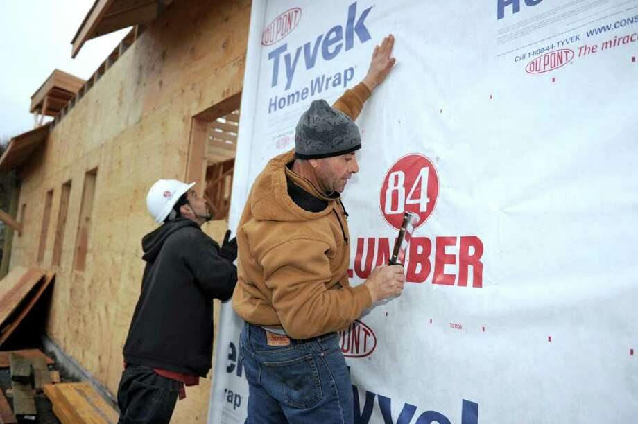 Robert Rodriguez, left, and Anthony Zavaglia, carpenters with Hayford Builders of Waterbury, attach insulation sheets to the walls of the new animal control facility that is being built on Old Farm Road in Newtown. Photo taken Tuesday, Dec. 27, 2011. Photo: Carol Kaliff / The News-Times