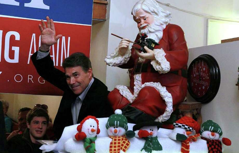 Texas Governor and Republican candidate for president Rick Perry waves to supporters during a campaign stop at the Main Street Cafe on December 27, 2011 in Council Bluffs, Iowa.  With one week to go before the Iowa caucuses, Perry continues his bus tour through the state. Photo: Justin Sullivan, Getty / 2011 Getty Images