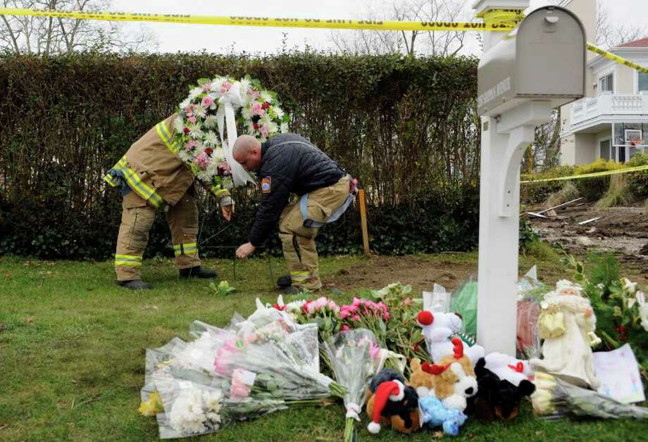 Firefighters lay a wreath in a memorial area outside the home of Madonna Badger in Stamford, Conn., Tuesday, Dec. 27, 2011.  A fire at the home on Christmas morning killed Badger's three daughters and parents. The Christmas Day fire was a tragic accident related to a fireplace in the home, not the result of foul play, Stamford Mayor Michael Pavia said Tuesday, Dec. 27, 2011. (AP Photo/Jessica Hill) Photo: Jessica Hill, Associated Press / Associated Press
