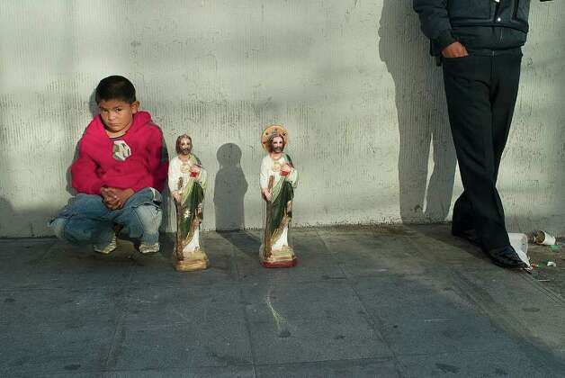 A young boy sells statues of Saint Jude Thaddeus, the patron saint of lost causes, outside the church of San Hipólito in the center of Mexico City where faithful believers gather for the feast day of the Cathiolic saint. In recent years, the devotion to the Apostle amongst poorer Mexicans has grown to almost cult-like proportions. Photo: Keith Dannemiller, For The Chronicle / ©2011 Keith Dannemiller