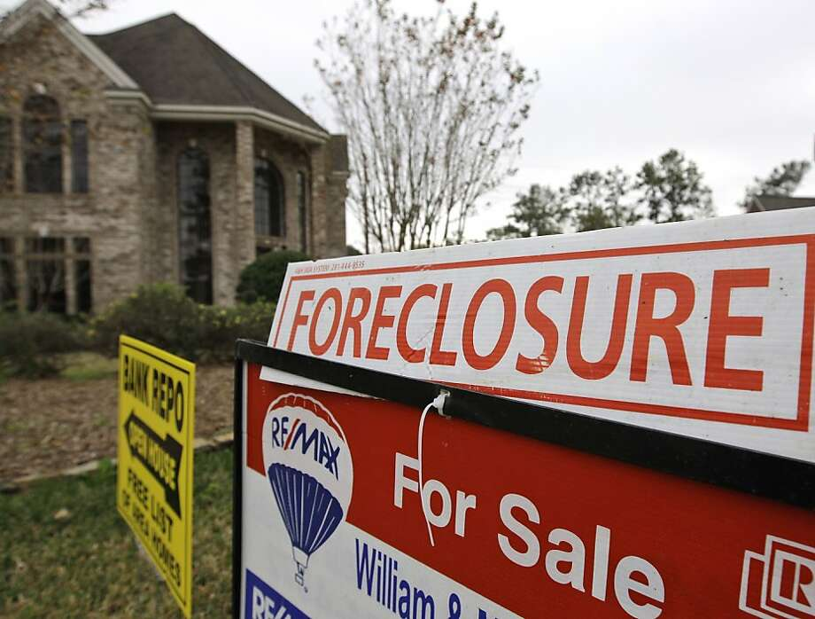 FILE - A Jan. 10, 2009 file photo shows a bank repo and foreclosure for sale signs outside a foreclosed home in Houston.  Foreclosure sales plunged 25 percent in the July-September quarter versus the April-June period and tumbled 31 percent from the third quarter last year, foreclosure listing firm RealtyTrac Inc. said Thursday, Dec. 2, 2010. Photo: David J. Phillip, AP