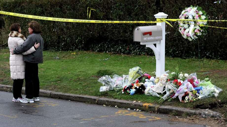 Area residents embrace near a memorial at the mailbox of Madonna Badger's home in Stamford on Tuesday, December 27, 2011, where a fire on Christmas morning killed Badger's parents and three daughters. Photo: Lindsay Niegelberg / Stamford Advocate
