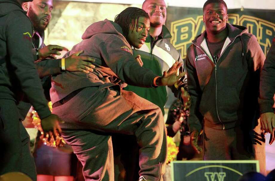 Baylor star quarterback R.G. Griffin III remains frozen in the Heisman Trophy pose which he struck for his teammates to carry him onstage at the Rudy's Bar-B-Q Pep Rally at the Arneson River Theater on the River Walk  on December 27, 2011. Photo: TOM REEL, SAN ANTONIO EXPRESS-NEWS / © 2011 San Antonio Express-News