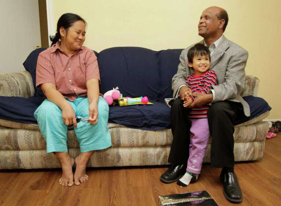 MELISSA PHILLIP : CHRONICLE BEARING GIFTS: Burma refugees Naw April Kyaw, left, and her daughter Naw Elizebeth, 2,  talk to Geleta Mekonnen, right, who brought gifts from Interfaith Ministries in Houston. Photo: Melissa Phillip / © 2011 Houston Chronicle