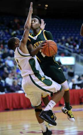 Trinity Catholic High School's Schadrac Casimir is fouled by New London's DeAnte Bruton Tuesday, December 27, 2011 during the Northeast Classic boys basketball tournament at the Webster Bank Arena in Bridgeport, Conn. Photo: Autumn Driscoll / Connecticut Post