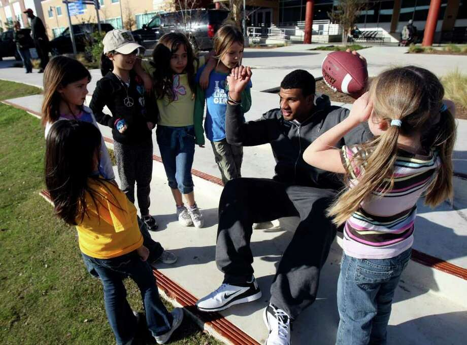 Baylor defensive end Kedrick Dial talks with children at Haven for Hope on Dec. 27, 2011 as he and some of hits teammates visited with families at the facility. Photo: HELEN L. MONTOYA, San Antonio Express-News / SAN ANTONIO EXPRESS-NEWS