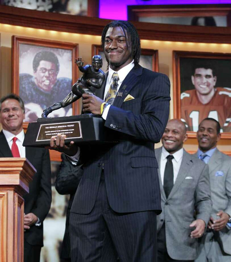 In this photo provided by the Heisman Trophy Trust, Robert Griffin III, of Baylor University, holds the Heisman Trophy award after being named the winner, Saturday, Dec. 10, 2011, in New York. Photo: AP