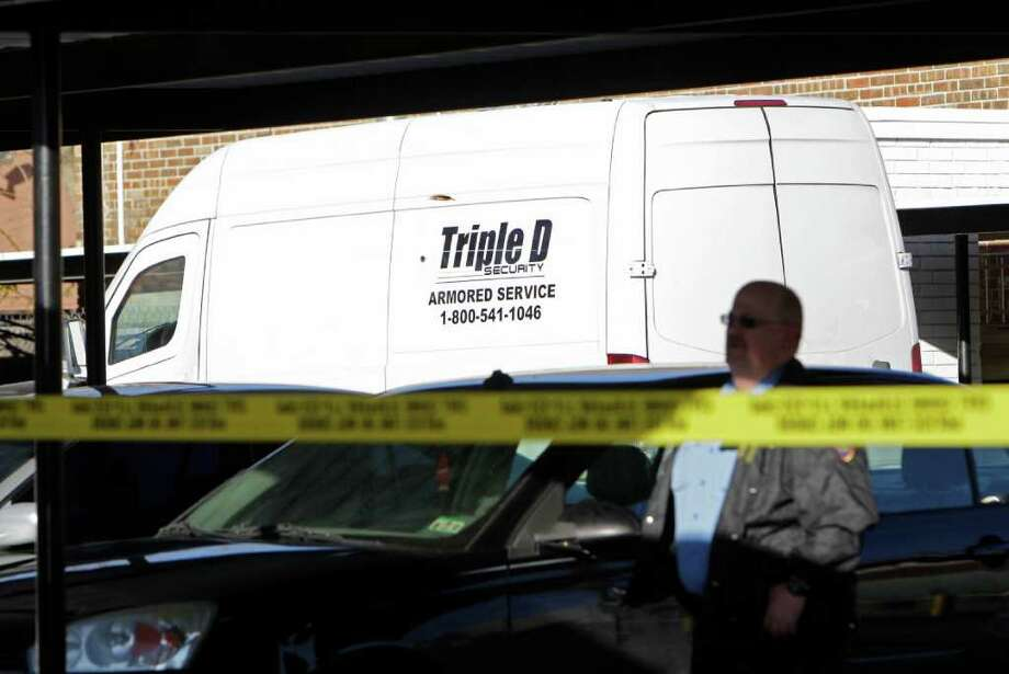 Houston police officers investigating a stolen armored van that was located at Colonial Apartments, 900 N. Durham, after it was taken from the fuel center at Kroger, 1035 N Shepherd Dr., Tuesday, Dec. 27, 2011, in Houston. ( Melissa Phillip / Houston Chronicle ) Photo: Melissa Phillip / © 2011 Houston Chronicle