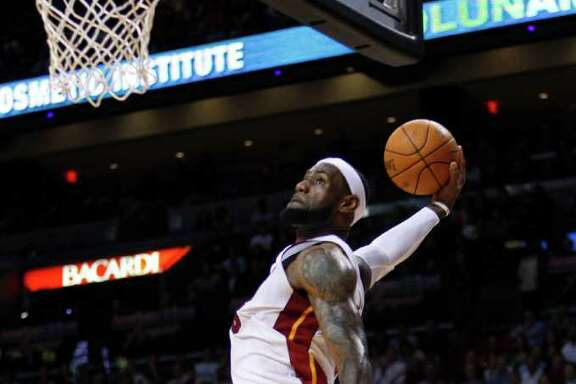 Miami Heat forward LeBron James drives in for a dunk against Boston Celtics forward Brandon Bass during the first half of an NBA basketball game, Tuesday, Dec. 27, 2011, in Miami. (AP Photo/Wilfredo Lee)