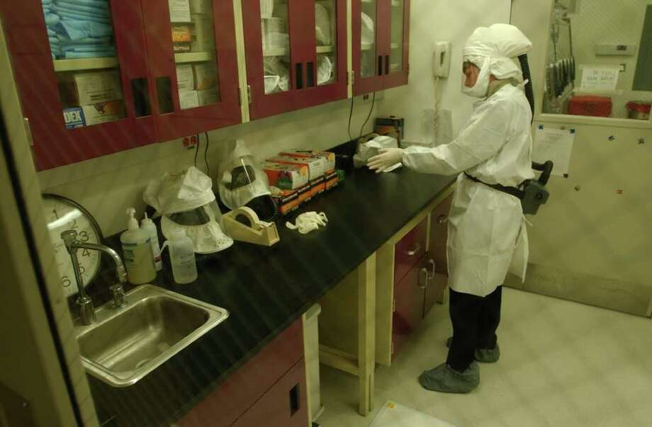 Times Union staff photo by Skip Dickstein -- A worker uses the appratus in the highly secure infectious disease area of the Wadsworth Lab in Albany, New York January 22, 2002 Photo: SKIP DICKSTEIN / ALBANY TIMES UNION