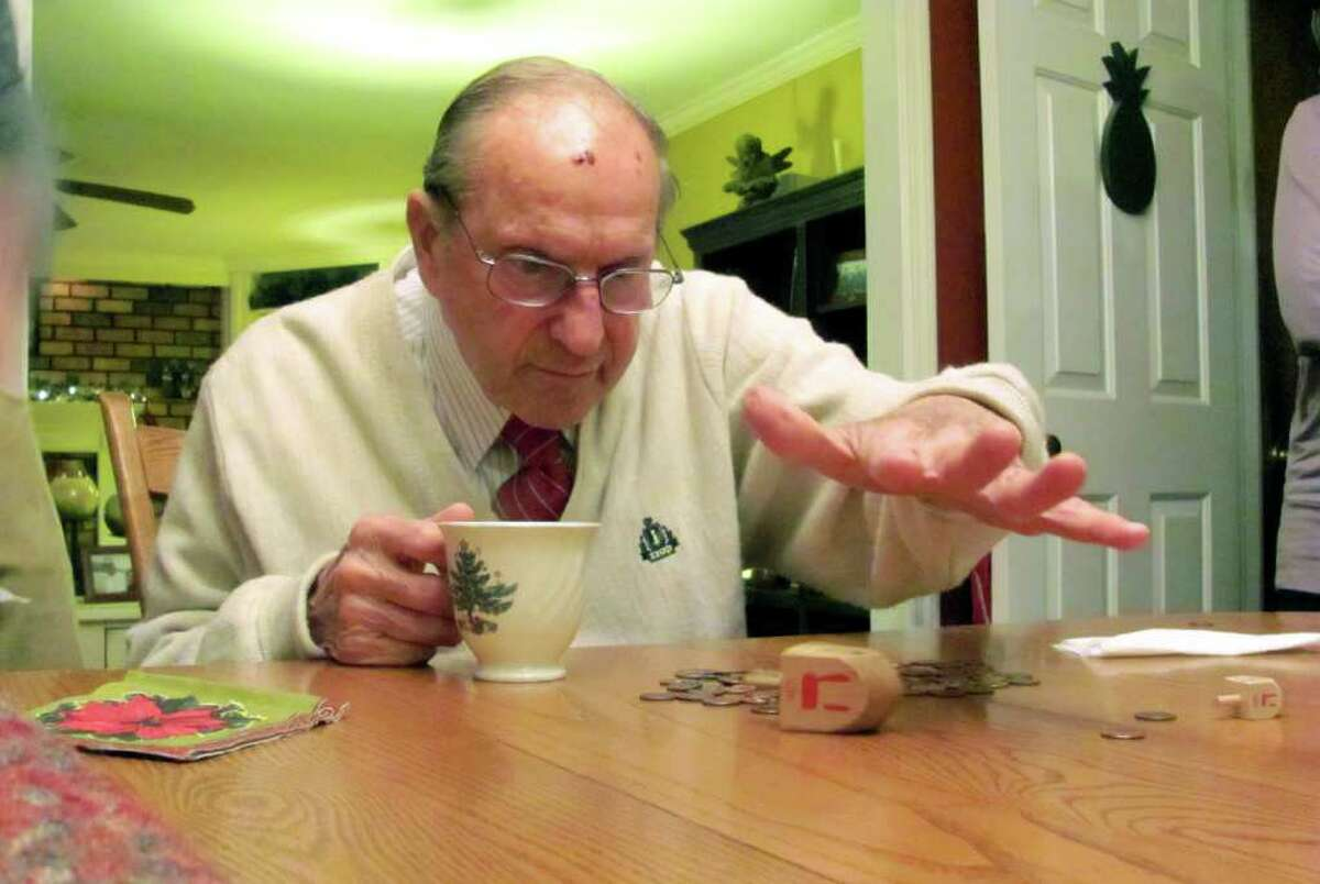 Alfred Lorini, 80, a retired Times Union printer, rolled 56 Gimel winners out of 68 rolls in a dreidel game on Christmas at the home of Chris Terry in Guilderland where Christian and Jewish family members gathered. The odds of Lorini rolling so many Gimels were 22.5 billion times 1 trillion. (Courtesy Leah Charash)