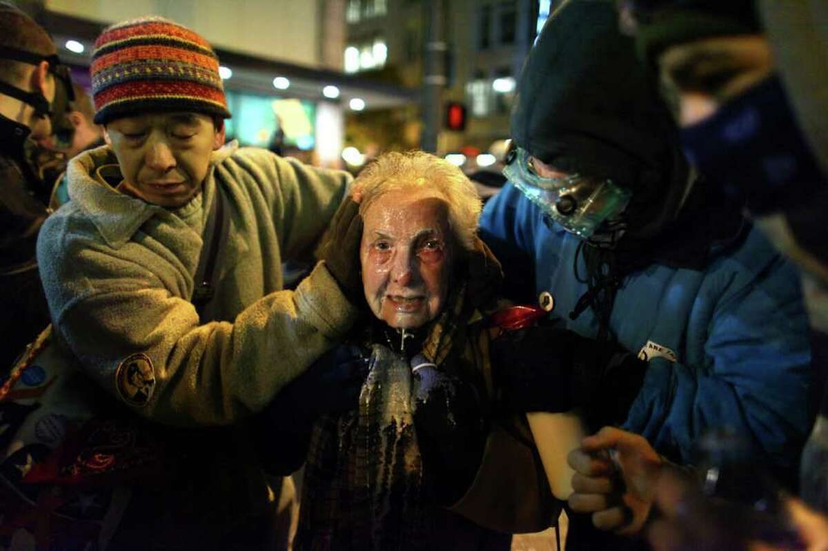 Seattle activist Dorli Rainey, 84, reacts after being hit with pepper spray during an Occupy Seattle protest on Tuesday, November 15, 2011 at Westlake Park. The Occupy movement resulted from simmering anger at financial institutions and frustration with a growing economic gap in the U.S. On the night Rainey was sprayed, protesters gathered in the intersection of 5th Avenue and Pine Street and many refused to move from the intersection after being ordered by police. Police then began spraying pepper spray into the gathered crowd hitting dozens of people. Rainey was rushed from the scene and had a milky substance splashed on her face after the spray hit her.