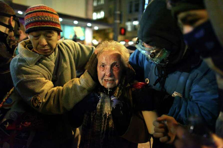 Seattle activist Dorli Rainey, 84, reacts after being hit with pepper spray during an Occupy Seattle