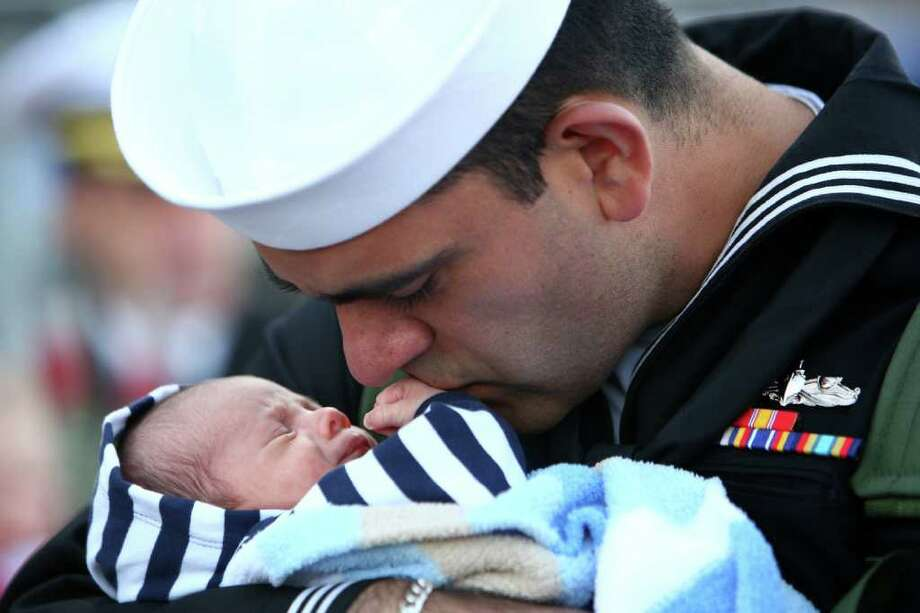 Nisse Fonseca meets his three week-old son Cuper for the first time as he is greeted by family after disembarking the U.S.S. Abraham Lincoln during the aircraft carrier's return to its home port on Thursday, March 24, 2011 at Naval Station Everett. The aircraft carrier was on a six-month deployment in the Western Pacific and U.S. Central Command areas of responsibility. The carrier later left Everett for its new home base on the East Coast. Photo: JOSHUA TRUJILLO / SEATTLEPI.COM