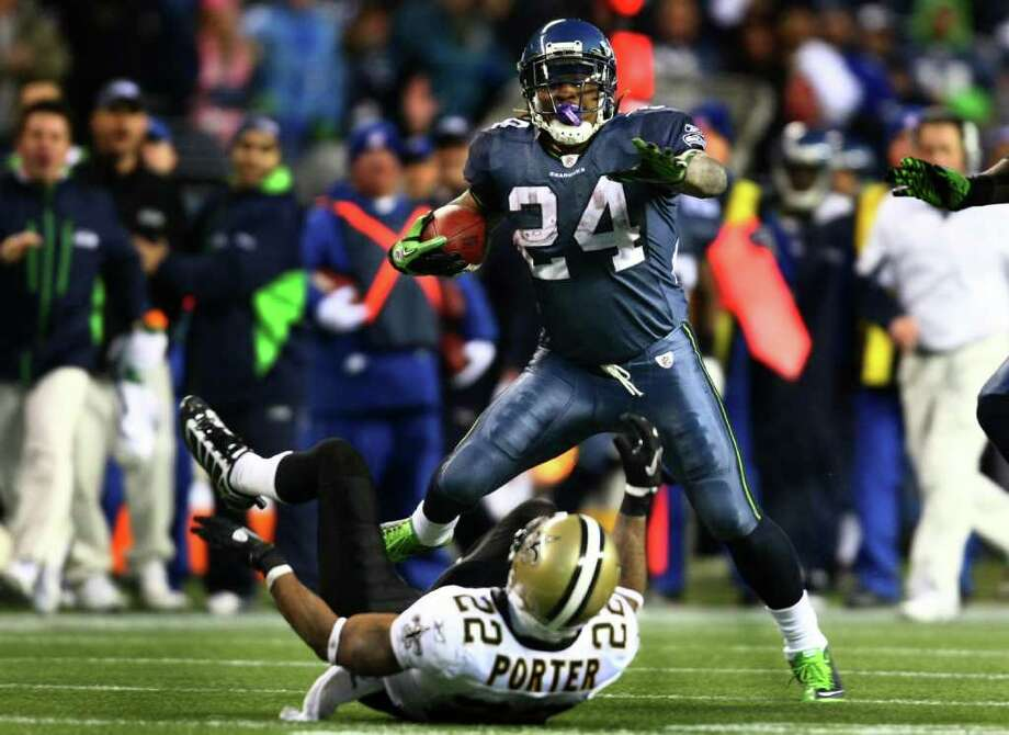 """Get off me!"" Seattle Seahawk Marshawn Lynch stiff arms New Orleans player Tracy Porter during an epic 67 yard touchdown run in the fourth quarter against the defending Super Bowl champs. The run by Lynch, which prompted cheering and stomping fans to register on a nearby seismometer, has been called one of the best runs in recent NFL history. The Hawks defeated the Saints 41 to 36 to advance in the playoffs. Photo: JOSHUA TRUJILLO / SEATTLEPI.COM"