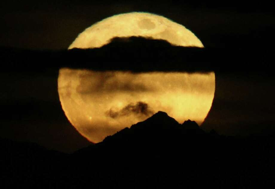 A 'super moon' rises over the Cascade Mountains on Saturday, March 19, 2011 in Seattle. The super moon happens when a full moon coincides with the perigee in the Moon's elliptical orbit. The Moon is closer to the Earth and appears bigger than normal. Photo: JOSHUA TRUJILLO / SEATTLEPI.COM