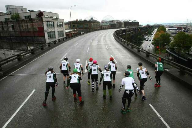 Members of the Rat City Rollergirls flat-track roller derby league skate on the upper deck of the closed Alaskan Way Viaduct on Saturday, October 22, 2011 in downtown Seattle. They were co-winners of a contest where organizations made pitches about what they would do on the deck of the closed highway for half an hour. The highway usually carries 110,000 cars per day and was closed for 9 days as demolition of the southern half of the aging structure began. The highway, built in the 1950s, will be replaced with a new deep bore tunnel along the Seattle waterfront. Photo: JOSHUA TRUJILLO / SEATTLEPI.COM