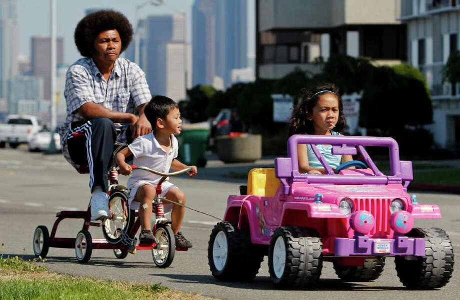 Youngsters give their dad a lift along Alki Beach in Seattle on Saturday, September 10, 2011 during a warm day. Photo: JOE DYER / SEATTLEPI.COM