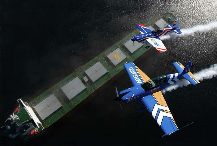 John Klatt in the Air National Guard Extra 300L, bottom right, and Bill Kerns in the Air Guard Staudacher, top right, fly over a ship in Seattle's Elliott Bay on Thursday, August 4, 2011. Stunt planes took to the skies of Seattle for the annual Seafair air show over Lake Washington. Photo: JOSHUA TRUJILLO / SEATTLEPI.COM