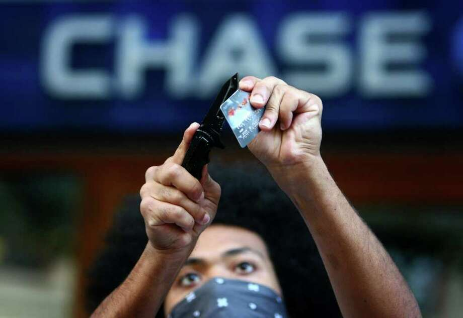 A protester cuts up a bank card during the Occupy Seattle protest in front of Chase Bank on 4th Avenue on Saturday, October 15, 2011 in Seattle. About 5,000 people joined protesters that had been camped at Westlake Park for two weeks. The day was dubbed as a global day of action by the movement. Photo: JOSHUA TRUJILLO / SEATTLEPI.COM